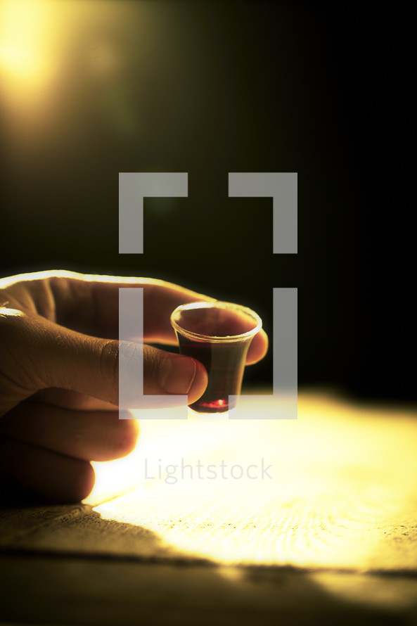 A hand holds a communion cup filled with wine as a light shines bright in the background.