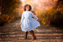 a little girl in a dress standing outdoors in fall