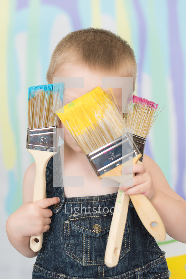 A little boy in overalls covering his face with paint brushes.