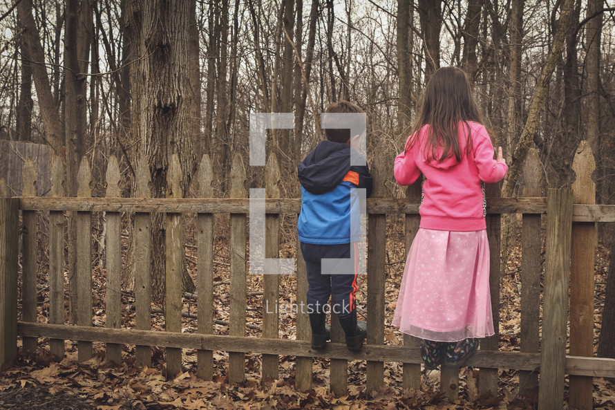kids standing on a fence to look over it
