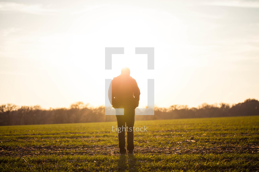 silhouette of a man in a field with his hands in his pockets and his head down