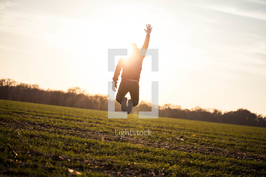 man jumping in a field with his hand raised to God under the glow of sunlight