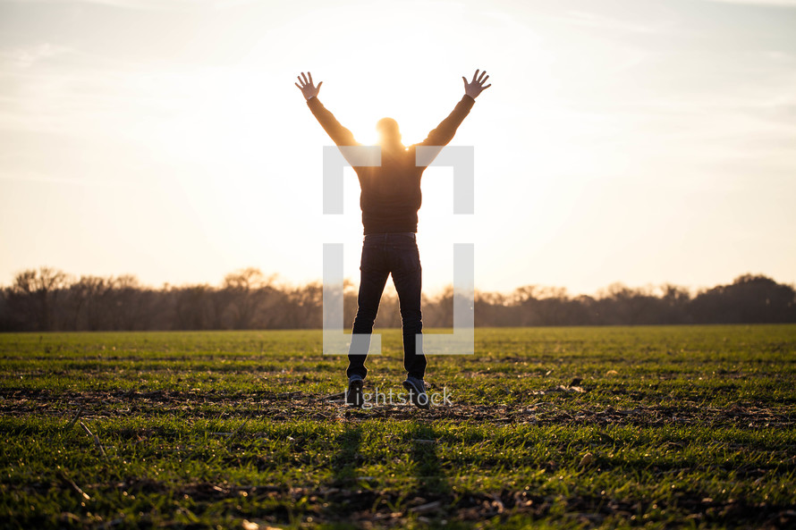 man jumping in a field with his hands raised