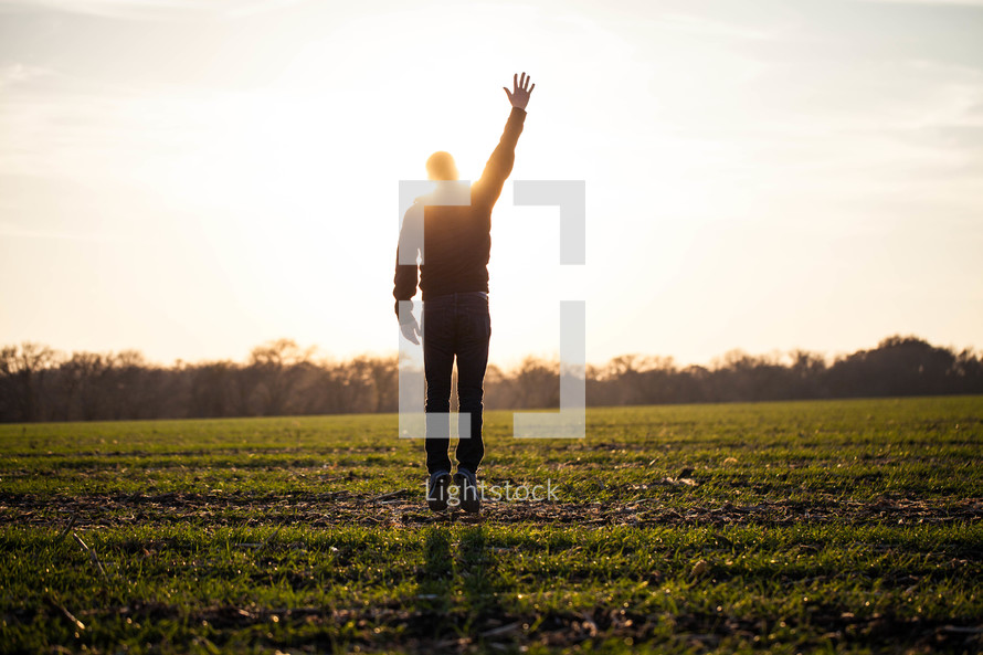 silhouette of a man jumping in a field with his hand raised to God