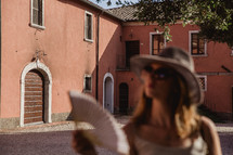 A woman fanning herself in a courtyard in Italy