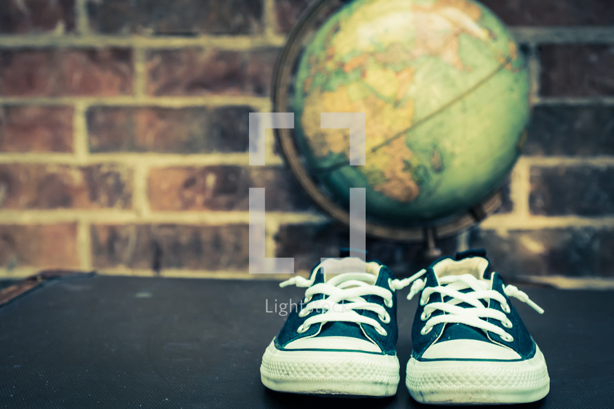 sneakers and globe on a trunk