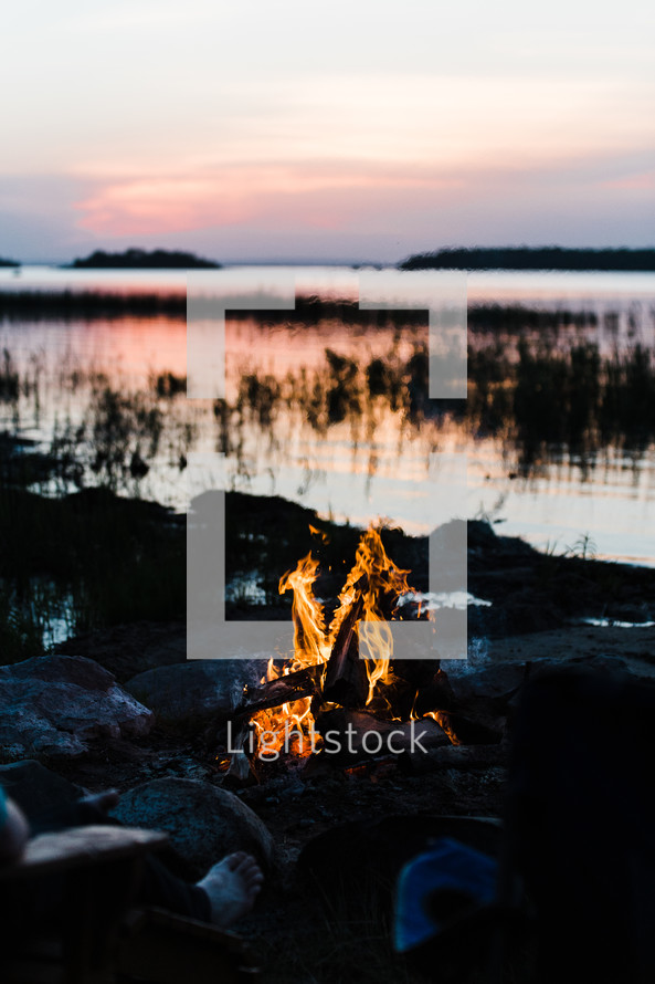 sitting by a campfire by a lake at dusk
