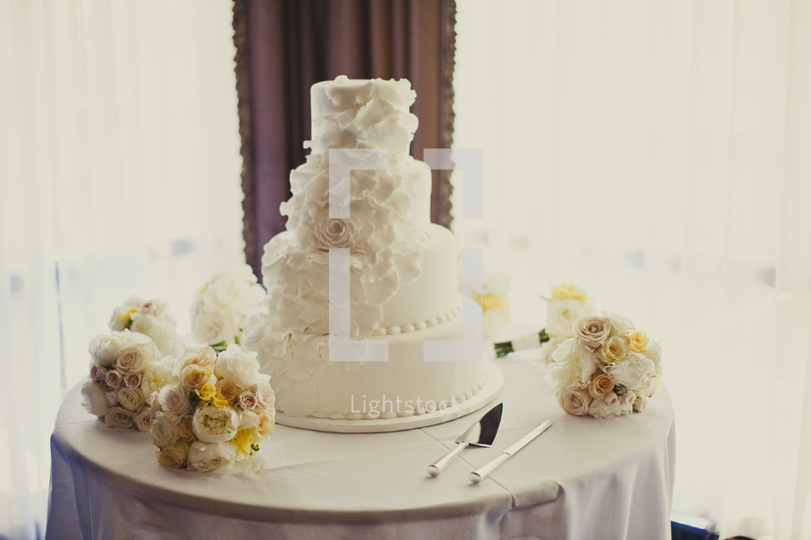 A wedding cake surrounded by flowers