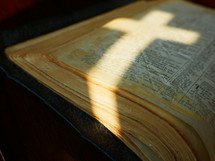 light in the shape of a cross on pages of a Bible