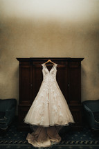 wedding gown hanging in a dressing room