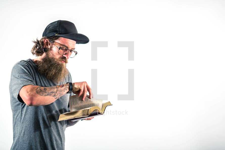 man with tattoos turning the pages of a Bible