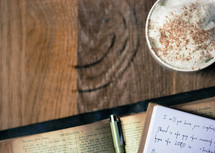 notes in a journal on an open Bible and latte