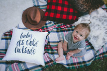 toddler girl sitting on a plaid blanket