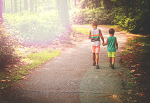 brothers walking holding hands on a trail