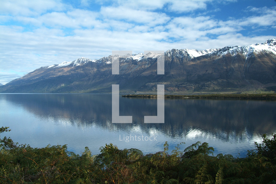 Snow capped mountain range across a calm lake