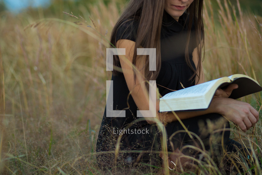 woman reading a Bible in a field