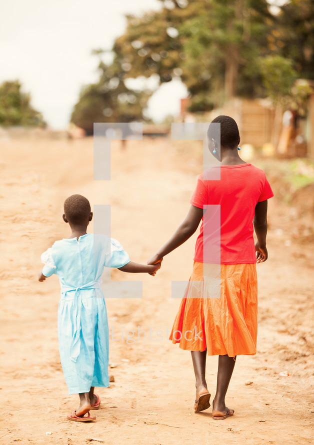 woman and girl walking holding hands on a dirt road