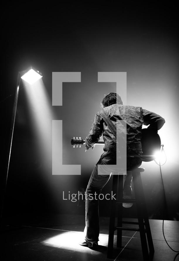 man under a spot light playing a guitar