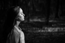 silhouette of a woman's side profile in darkness