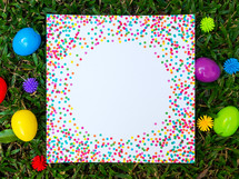 A colorful piece of paper and Easter eggs in green grass.