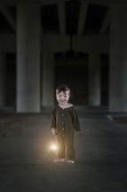 a toddler boy in pajamas holding a lantern