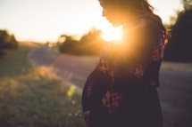 a pregnant woman standing outdoors with a sunburst behind her