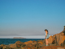 woman standing on rocks along Nelson Bay