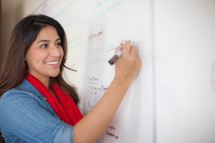 woman writing on a dry erase board