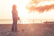 young girl standing on the beach holding her bible at sunset; thinking, nature, sunflare