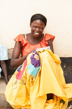 Smiling woman in a colorful dress.