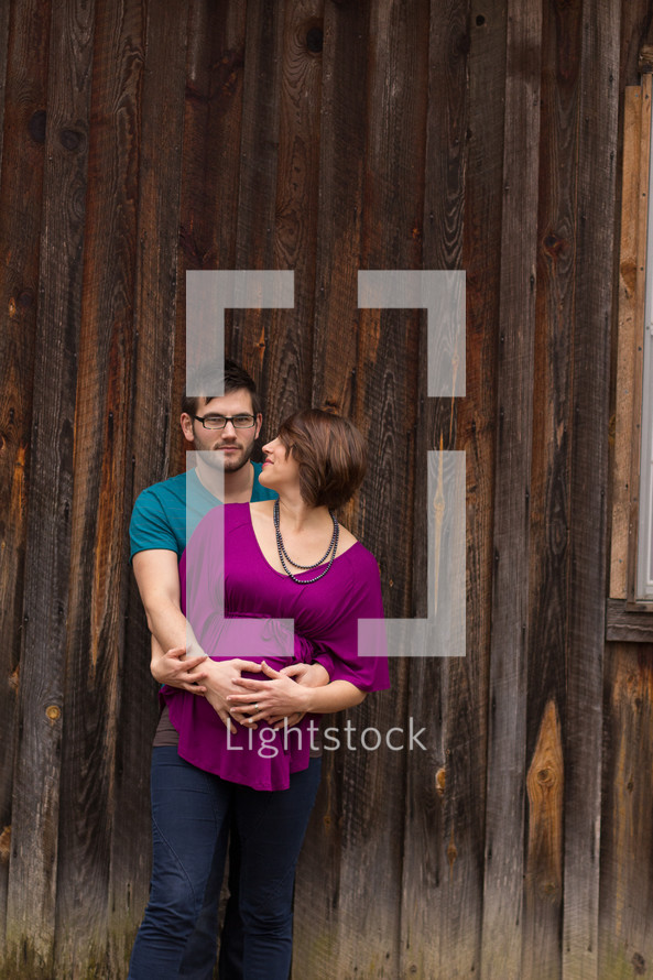 couple holding each other in front of a wooden wall