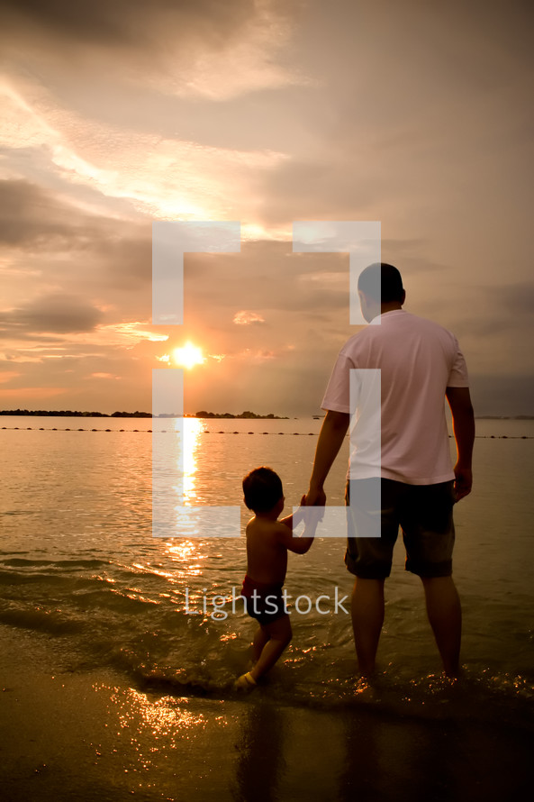 a father and son standing on a beach