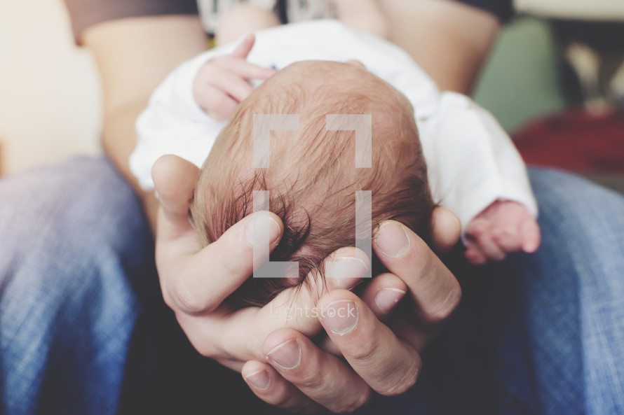 a father's hands cradling a newborn baby