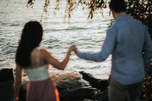 a couple holding hands on a rocky shore