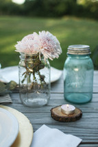 Flowers in a mason jar on a picnic table outside.