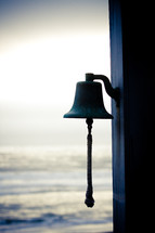 a bell and the ocean in the background