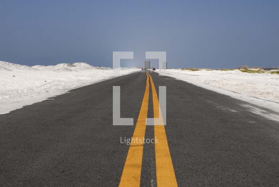 Open road through white sand dunes with double yellow lines