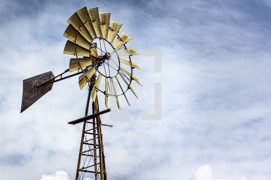 Windmill with golden glow from setting sun.