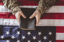 military man in uniform holding a Bible over an American flag