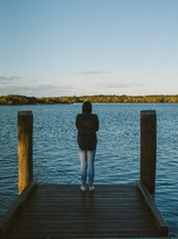woman standing at the end of a dock