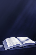 Open bible in beams of light with dust particles