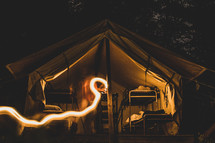streak of light and bunks in a tent