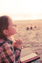 young girl praying on the beach with her bible; sunset