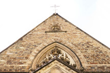Looking up at the gable roof of a Gothic-style church. A white cross sits at the head of the roof's ridge.