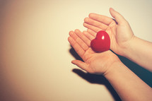 cupped hands holding a red heart