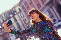 young woman with red hair and freckles takes a selfie in Piazza Pebliscito in Naples.