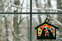 stained glass sun catcher children's craft hanging in a window