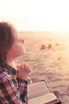 young girl praying with bible in lap, sitting in the sand at the beach beach, sunset