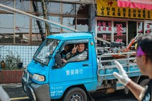man in a small truck in Taiwan giving a peace sign