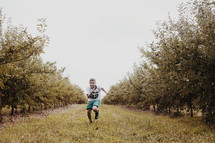 boy running in an orchard